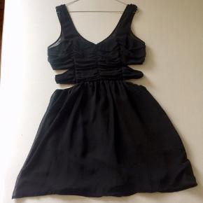 Festlig kjole med udskæringer i siden (de er ikke voldsomme, når kjolen er på). Overdelen er syet i corsage-stil, så kjolen sidder pænt og stoffet forneden falder super flot.