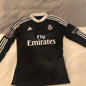 """Sælger denne sindssygt fede langærmede Real Madrid 3. trøje fra sæson 14/15, da den desværre er for lille til mig. Den er rimelig slidt (primært i tryk + brodering), men stadig brugbar. Uefa badges på begge ærmer er slidt og """"Bale 11"""" trykket på ryggen er faldet af, men kan stadig ses i det rigtige lys. På rykken er der ligeledes en mindre plet under trykket, som kan ses på billedet.  Kan afhentes i Hellerup eller sendes på købers regning med DAO."""