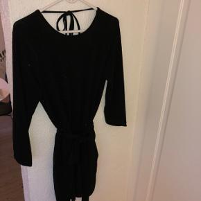 Jumpsuit, korte ben, åben ryg, bindebånd i taljen, sort med lidt glimmer. Kender ikke størrelsen da mærket er klippet af, men passer S/M - str.38 cirka