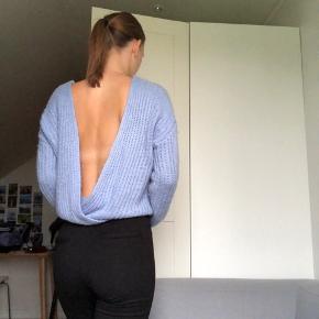 Fin lyseblå sweater med åben ryg og uden nogen tydelige tegn på slid