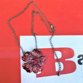 Halskæde med blomst i den dybeste, røde farve.  Matchende rød bling-sten i midten.  Sølvfarvet kæde og metalbase.  Kæden har variabel lukkelængde fra ca. 38 - 45 cm.  Halskæden har ikke været brugt, så nu sælges den billigt, så den kan komme ud i verden og leve.  Sælges for kun 35 kr. + evt. porto.  Kan afhentes på Frederiksberg.
