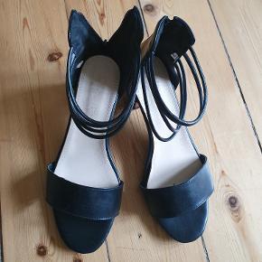 """Lækre sorte skindsandaler med """"træfarvet"""" hæl på 3,5 cm med lynlås i hælen. Skindet er blødt og sandalerne er derfor meget behagelige at have på. De er gode både til det pænere arbejdstøj og til fest. Sandalerne er for store og derfor kun prøvet på et par gange og aldrig brugt rigtigt."""