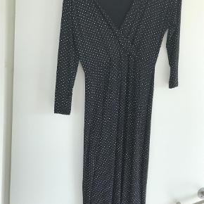 Brand: A  Varetype: Andet Størrelse: S/M Farve: Hvid,       Sort  Rigtig fin prikkede kjole sælges. Fremhæver taljen, og går pænt ned foran. Den er Vig forneden. Afhentes i Nordhavn. Kan sendes med GLS ved forudbetaling + køber betaler Porto. Jeg kan kontaktes på 42422704