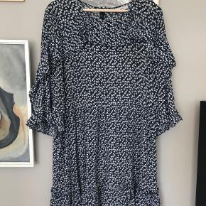 Smuk kjole i løst fit. Flæsedetaljer og med tre-kvart-ærmer. 100% viskose.