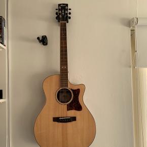 Akustisk CORT guitar, Grand Regal GA5F-MD Natrual. Taske og stativ følger med. Kvittering haves Den er købt den 8. August 2018. Det er en super god guitar med Pick up i. Den fejler ingenting, står fuldstændig som ny. Svarer kun på seriøse henvendelser.