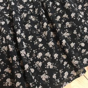 Løs nederdel med flæser og små blomster. Brugt 2-3 gange og fremstår som ny. Elastik i taljen, som måler 39cm fra søm til søm. Kan sendes eller afhentes i Aarhus C.