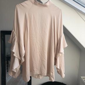 Der mangler en enkelt knap i nakken, men blusen bliver stadig lukket til i nakken med de to andre knapper