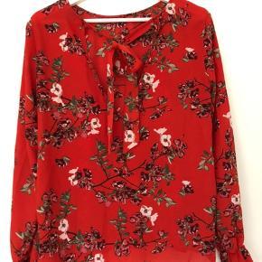 Flot rød bluse med blomster på. Ryggen går ned i et v og har bindebånd i halsudskæringen.  Byd gerne☺️