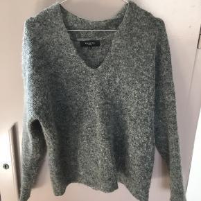 Strik i mørkegrå fra Selected Femme med rund hals. 38% uld, 28% mohair, 15% nylon, 15% polyester og 4% elastane