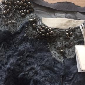 Smuk Smuk vest fra Heartmade Signature Pieces - Vesten er ubrugt og stadig med tags. Størrelse M/L.  Modellen er nogle år gammel, men meget klassisk og tidløs.  Stylenavn: Alexis signature Lamb fur capel.  Perlerne på vesten er sølv/grå. Skindet er: 100% Lamsbs Wool. Mål fra under ærme til under ærme når vesten er lukket: ca. 2 x 53 cm - længde fra skulder og ned foran: ca. 47 cm.  Nypris kr. 14.000,00 MP kr. 1.700,00 pp - Bytter ikke.
