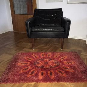 Lille og flot håndknyttet rya tæppe / måtte / forligger fra 70'erne. Røde og orange nuancer. Motivet er blomst / solsikke / morgenfrue - et meget klassisk mønster fra 60'erne / 70'erne. Fin stand - nogle tråde er let bleget i spidserne, men flot spil i farverne / luven. Længde 104 cm, bredde 70 cm.