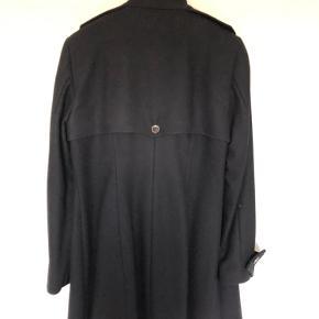 Elegant, klassisk uldfrakke i Sømandssnit fra Karen bySimonsen.  Frakken går til midt på låret og måler 88 bagpå og ned.  Den er kun brugt meget lidt og fremstår som næsten ny og er nyrenset. Bytter ikke.