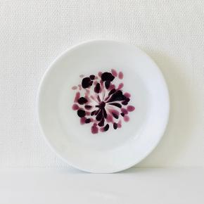 Smukt stort Afrikas Rose bordfad med lilla blomst. Designet af Per Lütken for Holmegaard Glasværk. Udført i  opal gals m/lilla blomst. Højde: 5,2 cm. Diameter: 34,4 cm. Vægt: 2958 gram. Signeret: Nej.