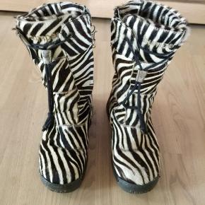Lækre zebrastribede støvler i moderne design. De er brugte men har mange gode kilometer til gode endnu. ☺️ den ene lynlåse hank er gået i stykker og erstattet af et lille hængsel.                     ( se billede) derfor den billige pris.