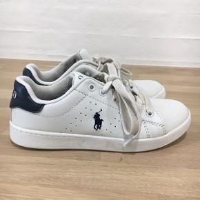 Hvide Polo Ralph Lauren sko i str. 33. Med mørkeblå logo. Rigtig god stand. Ingen ridder og skrammer men lidt beskidte snørebånd og indenunder forklappen.