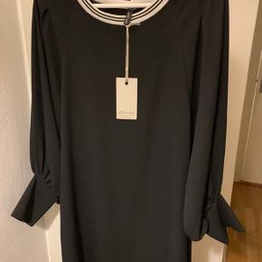 Sort elegant 'bluse' kjole fra italienske Anycase i str. One Size. Købt på rejse i april, men føles pænt for stor. Mål: længde ca 86-87 cm og bredde fra ærmegab til ærmegab ca 56 cm. Ærmer målt på indersiden inkl manchet del, som kan smøges op ca 50 cm.