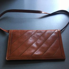 Vintage kernelæder håndtaske. Standen er er næsten perfekt på nær et par ridser foran på tasken. Mål: bredde: 29 cm. Højde: 18 cm. Dybde: 6 cm. Rem: 85 cm.