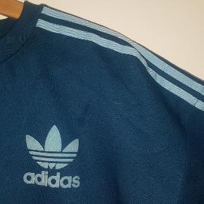 Flot petroleumsfarvet sweatshirt i lækker kraftig kvalitet med vildt blød inderside.  De klassiske adidas-striber og trefoil-logoet på forsiden er alle i en lys blå farve. Derudover er logoet i blød filt-lignende tekstur.