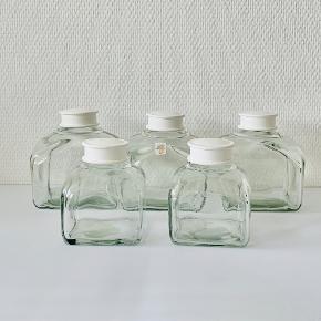 5 stk klare købmandsglas med hvide plast låg.  Designet af Michael Bang for Holmegaard. Mål:  3 købmandsglas: Højde: 11,5 cm. Diameter: 10,0 cm. 2 krydderurteglas: Højde: 7,2 cm. Diameter: 6,0 cm.