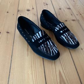 Brune og sorte loafers i str. 37 i ægte læder.  Brugt 1 gang!  Sælger til den hurtigste køber ⚡️  Køber betaler porto. Kan også hentes på min adresse i KBH S. Tæt på Amagerbro metro st.  Se også min profil og alle mine mange andre flotte og billige varer jeg har til salg 🌸  Tags: Multi - brun - brune - sort - sorte - loafer - sko - ballarina - ballerina - ballarinaer - ballerinaer - flats - flat - flade sko - zebra - dyreprint - læder - ruskind - lædersko - nitter - detaljer - metal - fest - work wear