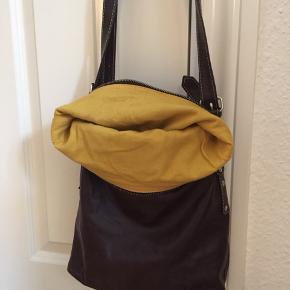 Onstage crossover taske i blødt skind. Mørkebrun med sennepsgult for. Yderlomme mes lynlås på bagsiden samt ekstra  inderrum med lynlås og mindre lomme. Nypris 1400,- Sælges da den ikke bliver brugt
