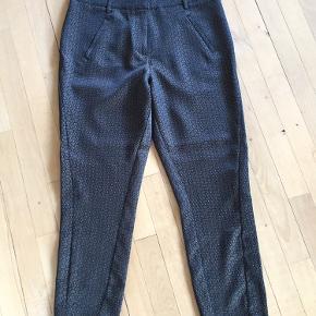 Str. 28. Bundfarve mørkeblå med mønster. Farven hedder navy blush. Model hedder. Angelie split. Lomme med lynlås i hver side. Pyntelommer bagpå Livvidde: 86 cm. Indvendig benlængde: 65 cm, udvendig benlængde: 91 cm
