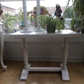 Super fint, hvidmalet og romantisk bord med søde detaljer og  udskæringer. (Lysestager følger ikke med)  Bordet måler: bredde 62cm, dybde 39cm og 48cm højt.