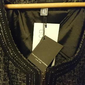 """Genoprettet med ny, lavere pris: Kun 500 alt inkl. for denne smukke blazer/jakke fra PBO; ret figursyet og med en masse bling og lækre detaljer. Sendes som forsikret pakke med TS/DAO.  Stadig tags på jakken. Har ikke fået taget mig sammen til at bruge den endnu. Den er simpelthen lidt for damet til mig. Den sidder ellers helt perfekt og passer mig virkelig godt (jeg er ca 100 cm om barmen og bruger 75E i BH). Synes nu mere det er en str. 40 end en str. 42. Svarer nok til en str. L, ikke XL!  Når jeg har prøvet den på, har jeg opdaget én mangel ved den: Inderforet glider ud gennem ærmegabet og skal lige """"møffes"""" op igen. Man kunne også hæfte det med et par sting indvendigt...  Pris: 500 alt inkl.  --- 0 ---  Se også alle de andre ting i sort, sølv, grå og guld, jeg sælger  blazer bouclé NY Farve: grå sølv bling Oprindelig købspris: 1500 kr."""