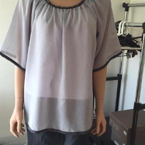 Varetype: Bluse Farve: Grå  100 % polyester        Brystvidde 50        Længde 70