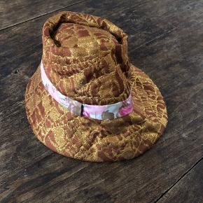 Smuk hat i guld og brun med bånd med rosa og pink mønster. Super sej, får den dog ikke brugt så den søger en ny glad ejer. Flotteste inderfoer i pink. Str. M.
