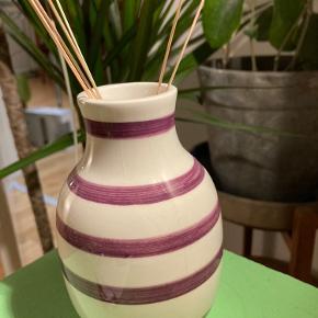 Kähler vase. 12cm. Hvid med lilla striber. Bittesmå revner nogle steder (ses på billede), ellers fejler den intet.