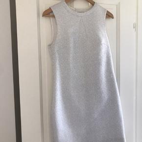 70'er inspireret kjole med flot snit både foran og bag. Med sølvglimmer i stoffet.