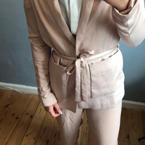 Lyserød/Rosa blazer fra H&M i skinnende blødt stof.  Knap i livet til at lykke og bånd som man enten kan binde bag på ryggen eller binde foran.  Afhentes i Sydhavnen eller sendes via DAO  Andet tøj på billedet er også til salg
