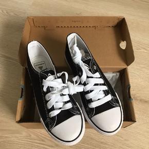 Sorte/hvide canvas sko, str. 33, Firefly, nye i æske (købt for små), nypris 199,- 10% af prisen går til Kræftens Bekæmpelse (Team Vejdik, Stafet For Livet) Se mere på mostermette.dk (IG812)
