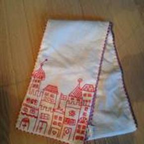 Tørklæde som ikk er brugt. På billedet ligger det dobbelt, så det er langt nok til, at man kan binde en knude med det.