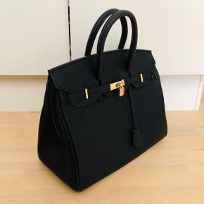 Helt ny håndtaske med gulddetaljer. 👛 👜  Specifikationen: - Kan bæres begge stram op fra siderne eller løs. - Låsen foran lukker og åbnes uden nøglen.  Inde i tasken er der meget plads - Der er også to lommer - en med lynlås og en åben. - Ikke læder, men meget høj kvalitet erstatning