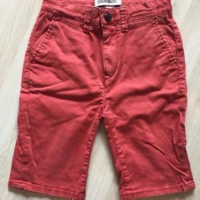 Rødlige Shorts der går ned til knæet. 98% Bomuld, 2% Elastik Str.128  Brugt få gange, men i go stand.