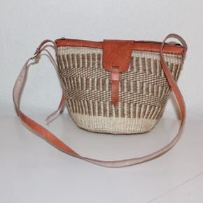 Smukke, håndlavede sisaltasker med detaljer i ægte læder fra Kenya. Læderrem kan justeres til den ønskede længde. Åbningen på tasken er ca. 30 cm. Den er foret indvendigt.  Bemærk at det er forskellige tasker, men næsten samme design   * Kan efter aftale afhentes i Brønshøj eller i Tølløse * Kan sendes