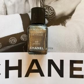 """Fin farve fra Chanel:  549 graphite . Kanten går mellem teksten """"les vernis"""" og """"nail colour , så der er stadig en del tilbage . Toplåg og æsken følger ikke med.  Kan sendes med Postnord som brev for 20 kr ved mobilpay. Søgeord: nail polish sølv les vernis colour neglelakker neglelak graphite skimmer glimmer"""