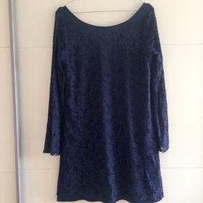 Fin mørkeblå blonde-kjole med dyb ryg, som kun er brugt få gange.  Lange ærmer, som er syet med lidt vidde forneden. Ærmerne er af gennemsigtig blonde.