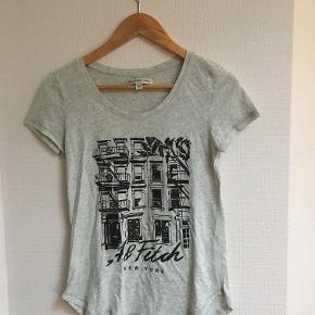 """Lysegrå t-shirt fra Abercrombie & Fitch i str XS, passer fint en S også. Der sidder """"palietter"""" uden på mønsteret. Brugt meget få gange."""