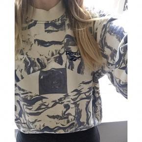 Vintage Reebok sweatshirt i råhvid med blåt print. Jeg kan ikke finde en størrelse i den, men jeg bruger normalt 40 og den passer mig som på billedet. Den har ligesom det meste vintage tøj, tegn på brug - misfarvninger ved kraven, som det også ses på billederne.  Sender gerne med DAO :)