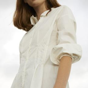 Den flotteste, elegante og flatterende skjorte fra PROEM Parades.  PROEM Parades er et nyt dansk mærke, der har fokus på bæredygtighed og etiske forhold. Tøjet bliver lavet i begrænset omfang og til den enkelte bestilling i bæredygtige restmaterialer. Skjorten er i lækker poplinbomuld.  Enkelt, klassisk og unik.  Skjorten er størrelse 2, hvilket svarer til en medium.   Den er aldrig brugt og har stadig prismærke siddende. Nypris var 1000 kr.