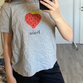 """Grå t-shirt fra & other stories hvorpå der er et jordbær og skriften """"fraise"""", fitter str M 🌸"""