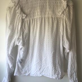 Smuk hvid skjorte med elegante detaljer fra Etoile Isabel Marant. Skjorten har flotte voluminøse ærmer og er flot både alene, eller med en tætsiddende strik over. Det er en fransk str. 36, ca. svarende til en dansk str. 34/small.  Skjorten er brugt, men med få brugstegn - her utydelig gule plamager ved ærmerne.    Fra ikke-ryger hjem.  Kom med et bud!
