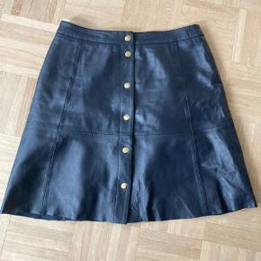 Smukt mørke blåt læder skirt, fra Selected Femme. Gennem knappet med guld farvet trykknapper.  100% læder og størrelse medium.  Afhentes i Vejle eller sendes med DAO -køber betaler fragt