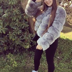 Grå faux fur jakke.  Aldrig brugt, helt NY Uden hætte  Str. 38 men passer en str. 36 Købt for 1.300 kr.  Lukkes med hægter foran   BYD.   Kan hentes på Frederiksberg :-)