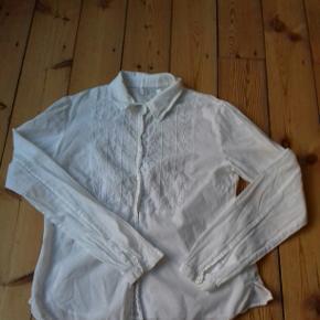 Fin hvid skjorte med lidt flæser øverst og knapper hele vejen ned.