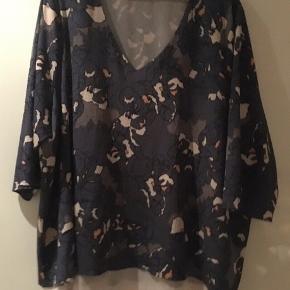 Super fin let bluse til hverdag eller fest. I tyndt luftigt stof i flere lag. Bryst 71 x2 =142cm. Længde ryg= 80cm.