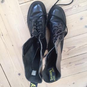 Høj Dr. Martens støvle i sort læder.  Trænger til nye snørebånd
